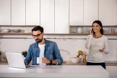 Γενειοφόρο άτομο που χρησιμοποιεί το lap-top στην κουζίνα στοκ φωτογραφία με δικαίωμα ελεύθερης χρήσης