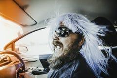 Γενειοφόρο άτομο σε μια μπλε περούκα πίσω από τη ρόδα Στοκ Φωτογραφίες
