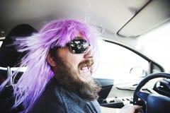 Γενειοφόρο άτομο σε μια ρόδινη περούκα πίσω από τη ρόδα Στοκ φωτογραφίες με δικαίωμα ελεύθερης χρήσης