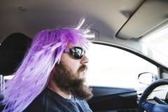 Γενειοφόρο άτομο σε μια ρόδινη περούκα πίσω από τη ρόδα Στοκ φωτογραφία με δικαίωμα ελεύθερης χρήσης