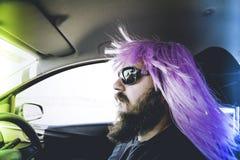 Γενειοφόρο άτομο σε μια ρόδινη περούκα πίσω από τη ρόδα Στοκ Φωτογραφία