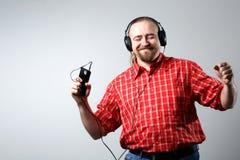 Γενειοφόρο άτομο στα ακουστικά που ακούει τη μουσική στοκ φωτογραφία