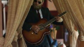 γενειοφόρο άτομο στη μαύρη κιθάρα παιχνιδιών κοστουμιών μεταξύ των κουρτινών απόθεμα βίντεο