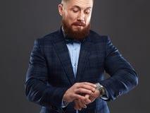 Γενειοφόρο άτομο στο κοστούμι που περιμένει και που εξετάζει το ρολόι Στοκ Εικόνα