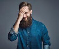 Γενειοφόρο άτομο στο μπλε πουκάμισο τζιν με το χέρι στο κεφάλι Στοκ Εικόνες