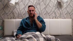 Γενειοφόρο άτομο στο πράσινο ή σκούρο μπλε μπουρνούζι που μιλά με το τηλέφωνο και τον καπνό το ηλεκτρονικό τσιγάρο στο κρεβάτι απόθεμα βίντεο
