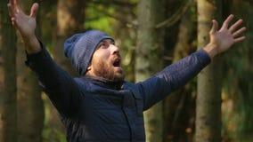 Γενειοφόρο άτομο στο σακάκι και το πλεκτό καπέλο αυξάνοντας τα χέρια της επάνω δυνατά που κραυγάζουν ενεργά γιορτάστε το επίτευγμ απόθεμα βίντεο