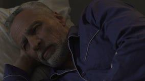 Γενειοφόρο παλαιό αρσενικό που βρίσκεται άγρυπνο σε ανίκανο κρεβατιών να πέσει κοιμισμένο τη νύχτα sleeplessness απόθεμα βίντεο