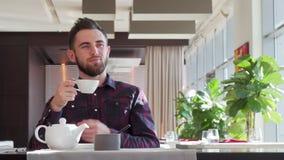 Γενειοφόρο όμορφο άτομο που κοιτάζει μακριά σκεπτικά, που απολαμβάνει το τσάι πρωινού απόθεμα βίντεο