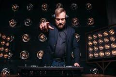 Γενειοφόρο DJ στη μουσική παιχνιδιών αναμικτών στο κόμμα λεσχών Στοκ Φωτογραφία