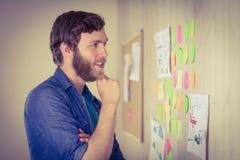 Γενειοφόρο hipster που εξετάζει τον τοίχο καταιγισμού ιδεών Στοκ φωτογραφία με δικαίωμα ελεύθερης χρήσης