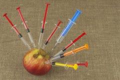 Γενετική έννοια τροποποίησης Φρούτα και syginge Apple που λαμβάνει μια έγχυση κάποιας ουσίας για τη γρήγορη ωρίμανση Στοκ εικόνα με δικαίωμα ελεύθερης χρήσης