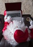 Γενικά έξοδα της χαλάρωσης Άγιου Βασίλη στον καναπέ στο σπίτι Χρησιμοποίηση του lap-top φ στοκ εικόνες