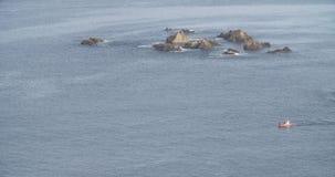 Γενική άποψη της θάλασσας με μια βάρκα που διασχίζει την με τους βράχους κοντά σε την απόθεμα βίντεο