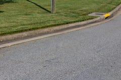 Γενική οδός και σκουπίζοντας συγκράτηση, πράσινη χλόη και κίτρινος αγωγός στοκ εικόνα με δικαίωμα ελεύθερης χρήσης