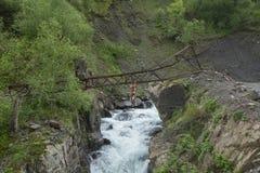 Γενναία ένωση ατόμων πέρα από έναν ποταμό βουνών στη Γεωργία Στοκ Εικόνες