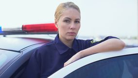 Γενναία αστυνομικίνα που στέκεται κοντά στο περιπολικό αυτοκίνητο, προστασία της δημόσια τάξης στην πόλη απόθεμα βίντεο