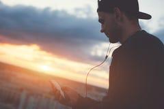 Γενναία συνεδρίαση ατόμων επάνω από την πόλη με τη μουσική smartphone και ακούσματος Στοκ φωτογραφία με δικαίωμα ελεύθερης χρήσης
