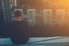 Γενναία συνεδρίαση ατόμων και κατάψυξη στην άκρη της στέγης στο ηλιοβασίλεμα Στοκ εικόνα με δικαίωμα ελεύθερης χρήσης