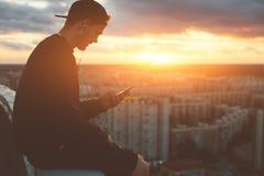 Γενναία συνεδρίαση ατόμων και κατάψυξη στην κορυφή της στέγης στο ηλιοβασίλεμα Στοκ Φωτογραφία