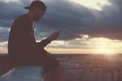 Γενναία συνεδρίαση ατόμων στην άκρη της στέγης με τη μουσική smartphone και ακούσματος Στοκ Φωτογραφία