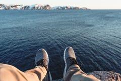 Γενναία συνεδρίαση ατόμων στον απότομο βράχο μπροστά από τη θραύση επάνω από τα βουνά θάλασσας και χιονιού Στοκ φωτογραφία με δικαίωμα ελεύθερης χρήσης