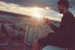 Γενναία συνεδρίαση ατόμων χαμόγελου στην άκρη της στέγης με τη μουσική smartphone και ακούσματος Στοκ φωτογραφία με δικαίωμα ελεύθερης χρήσης