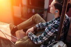 Γενναία συνεδρίαση ταξιδιωτικών ατόμων στη μουσική στεγών και ακούσματος στο κινητό τηλέφωνό του Στοκ φωτογραφία με δικαίωμα ελεύθερης χρήσης