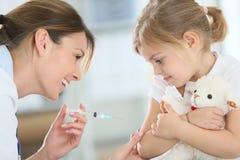 Γενναίο μικρό κορίτσι που λαμβάνει την έγχυση από το γιατρό στοκ εικόνες