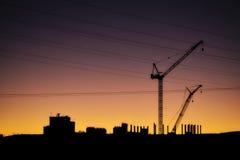 Γερανοί, ηλεκτροφόρα καλώδια και βιομηχανικά εργοστάσια που σκιαγραφούνται ενάντια στο ηλιοβασίλεμα Στοκ εικόνα με δικαίωμα ελεύθερης χρήσης