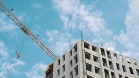 Γερανοί κατασκευής για να στηριχτεί σε ένα υπόβαθρο του μπλε ουρανού με τα άσπρα σύννεφα απόθεμα βίντεο