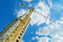 Γερανοί κατασκευής και ατελές σπίτι Στοκ εικόνα με δικαίωμα ελεύθερης χρήσης