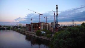 Γερανοί κατασκευής στο ηλιοβασίλεμα από τον ποταμό 4K φιλμ μικρού μήκους