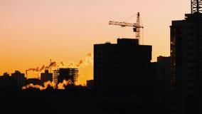 Γερανοί που λειτουργούν στους κατοικημένους κατασκευαστές εργοτάξιων οικοδομής που απασχολούνται στη χρυσή ώρα φιλμ μικρού μήκους