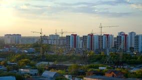 Γερανοί πύργων η περιοχή στη σύγχρονη πόλη ενάντια στο ηλιοβασίλεμα απόθεμα βίντεο