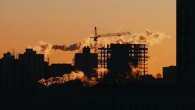 Γερανοί πύργων που λειτουργούν στους χτίζοντας κατασκευαστές κτημάτων κατασκευής που εργάζονται στην ανατολή ή το ηλιοβασίλεμα απόθεμα βίντεο