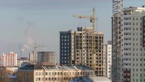 Γερανοί πύργων που λειτουργούν στο κατοικημένο κτήριο κτημάτων εργοτάξιων οικοδομής, εργασία κατασκευαστών κτηρίου απόθεμα βίντεο
