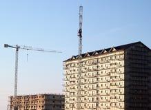 Γερανοί στα κτήρια που καλύπτονται δίπλα στα ικριώματα Στοκ Εικόνα