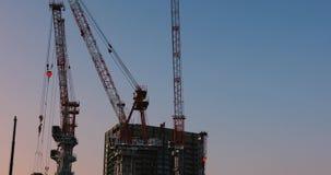 Γερανοί στην κατώτερη κατασκευή στον ευρύ πυροβολισμό του Τόκιο στο σούρουπο απόθεμα βίντεο