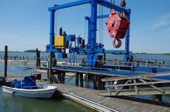 Γερανός και βάρκα αποβαθρών με τη ναυτική άποψη Στοκ Φωτογραφία