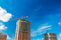 Γερανός και πολυκατοικία κάτω από τις οικοδομές ενάντια στο μπλε ουρανό ήλιων Στοκ Εικόνα