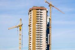 Γερανός και πολυκατοικία κάτω από τις οικοδομές ενάντια στο μπλε ουρανό ήλιων Στοκ φωτογραφίες με δικαίωμα ελεύθερης χρήσης