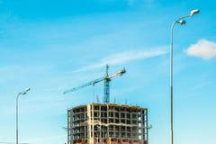 Γερανός και πολυκατοικία κάτω από τις οικοδομές ενάντια στο μπλε ουρανό ήλιων Στοκ Φωτογραφίες