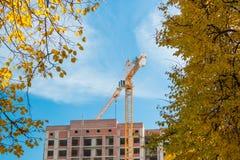 Γερανός και πολυκατοικία κάτω από τις οικοδομές ενάντια στο μπλε ουρανό ήλιων Στοκ εικόνα με δικαίωμα ελεύθερης χρήσης