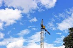 Γερανός κατασκευής ενάντια στο μπλε ουρανό με τα άσπρα σύννεφα Στοκ εικόνα με δικαίωμα ελεύθερης χρήσης