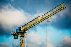 Γερανός κατασκευής ενάντια στο νεφελώδη μπλε ουρανό Στοκ Φωτογραφίες