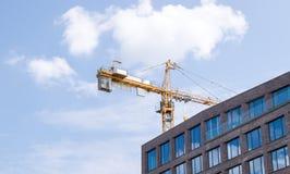 Γερανός κατασκευής και ένα σπίτι οικοδόμησης ενάντια στον ουρανό Στοκ φωτογραφία με δικαίωμα ελεύθερης χρήσης