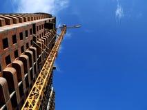 Γερανός κατασκευής που στηρίζεται πλησίον στο υπόβαθρο μπλε ουρανού Στοκ Φωτογραφίες