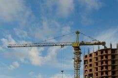 Γερανός κατασκευής στο εργοτάξιο οικοδομής ενός κατοικημένου σπιτιού τούβλου στοκ φωτογραφίες