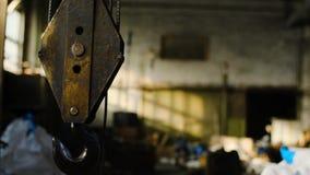 Γερανός μέσα στην αποθήκη εμπορευμάτων r Παλαιός σκουριασμένος γάντζος γερανών που αναστέλλεται στο υπόβαθρο της εγκαταλειμμένης  απόθεμα βίντεο